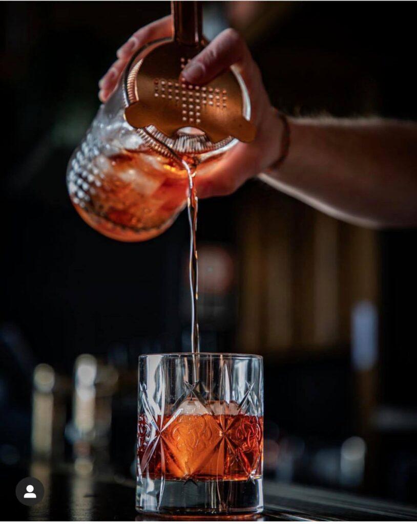 nalewanie gotowego negroni do szklanki z pomocą strainera lub sita