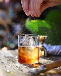 wyciskanie skórki pomarańczy do drinka negroni